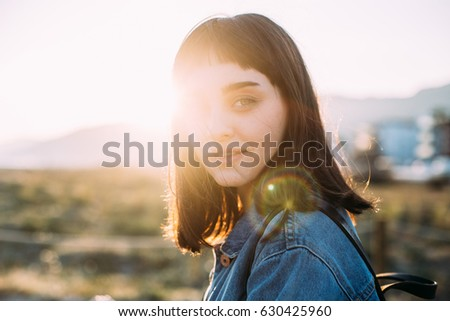 Portrait of a small hipster girl with dark hair and bangs wearing denim jacket and backpack, student, large lens flare in yellow orange sunlight near the sea with bokeh city in the background.