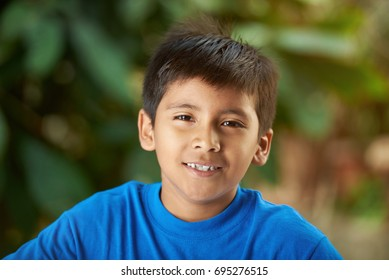 Portrait of small hispanic boy in blurred sunny background
