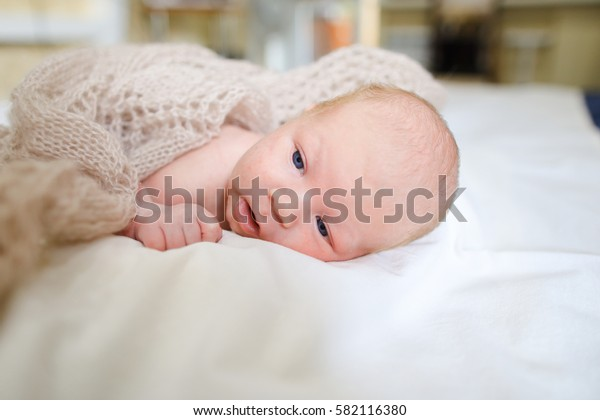 Portrait of small newborn baby boy covered beige knitted blanket and which lies on white bed in sleeping room. Concept of Maternal Love, Affection, Beginning Life, Cognition Surrounding World.