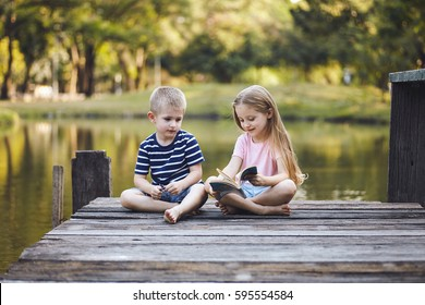 Portrait small preschool boy and girl relaxxing with book near the lake in country side