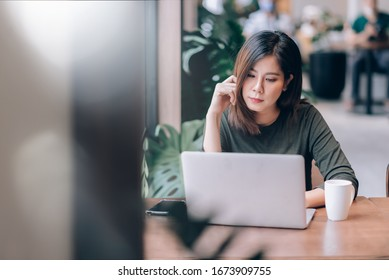 Portrait of Smart Asian Woman Freelance Online Working with Laptop in Co-Working Space