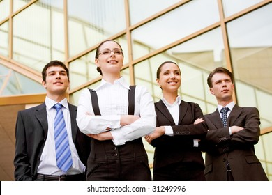 Portrait of smart associates standing in row and looking forwards with successful woman in front
