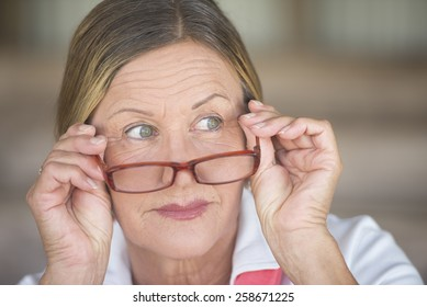 Portrait smart attractive mature business woman with glasses and curious observing expression, blurred background.