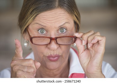 Portrait smart attractive mature business woman or dominant teacher with glasses and angry upset expression, blurred background.