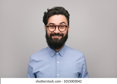 Portrait of smart bearded man in blue shirt and glasses smiling at camera on white.