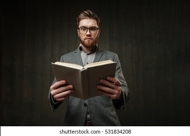 Portrait of a smart bearded man in casual suit holding book isolated on the black wooden background