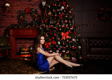 95ad13a1be29 portrait of the smart brunette in a brilliant dress against the background  of a Christmas fir