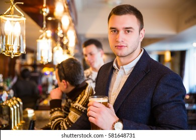Portrait of smart business man drinking beer in bar
