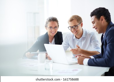 Portrait of smart business partners using laptop at meeting