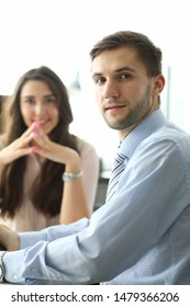 Portrait of smart businessman sitting in company office and discussing profitable contract with pretty businesswoman. Male looking at camera with happiness. Biz meeting concept. Blurred background