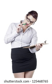 Portrait of a smart businesswoman holding a clipboard and biting her pen