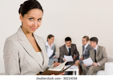Portrait of smart businesswoman looking at camera on background of working colleagues