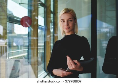 Portrait of smart businesswoman resting after development project on digital tablet while standing near office conference room, successful female financier holding touch pad after her presentation