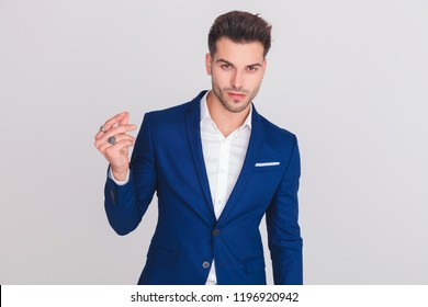 portrait of smart casual man in blue suit snapping his fingers while standing on light grey background