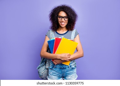 Portrait of smart educated girl with beaming smile in denim outfit eyewear having colorful textbooks in hands looking at camera isolated on violent background. Training skills high-school concept