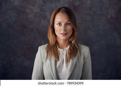 Portrait of smart elegant woman standing against dark background