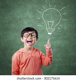 Portrait of a smart elementary school student pointing at a lamp picture on the chalkboard