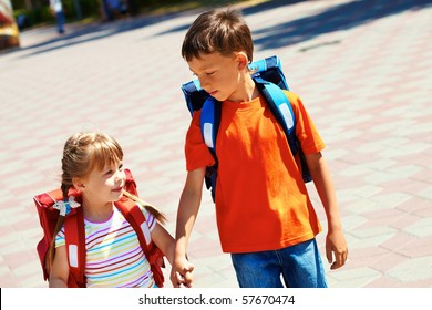 Portrait of smart friends with backpacks walking down city road on sunny day