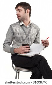 Portrait of smart fun young male executive sitting on chair isolated against white background,