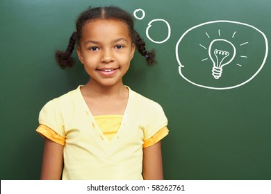 Portrait of smart girl by the blackboard thinking of light idea and looking at camera