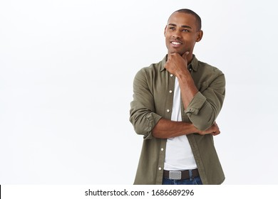 Portrait of smart handsome african-american man, touch chin and smiling pleased as found excellent choice, pondering decision, thinking over white background, thoughtful face