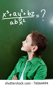 Portrait of smart lad looking at blackboard with algebraic formula on it