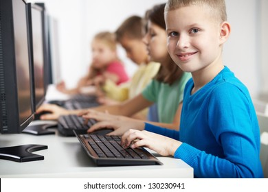 Portrait of smart lad looking at camera at computer lesson