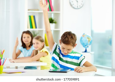 Portrait of smart lad at workplace raising hand and looking at touchpad with his classmates on background