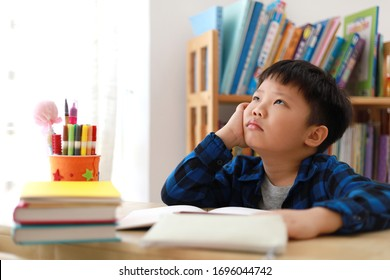 Portrait of smart little Asian boy thinking with eyes looking up while doing homework. Education concept.