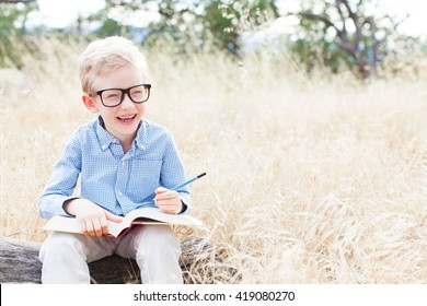 portrait of smart little boy in glasses holding book ready for school enjoying autumn park with copy space at his side