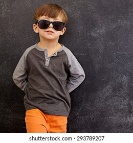 Portrait of smart little boy wearing sunglasses smirking. Cool kid in shades leaning on a blackboard looking at camera smiling with copy space.