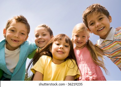 Portrait of smart preschoolers embracing each other on background blue sky