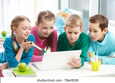 Portrait of smart schoolgirls and schoolboys looking at the laptop in classroom