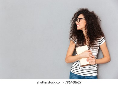 Portrait of smart smiling woman in eyeglasses holding books in hands being delighted to pass exams successfully, isolated over grey wall copy space