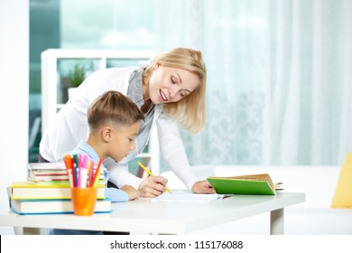 Portrait of smart tutor with pencil correcting mistakes in pupil�¢??s notebook