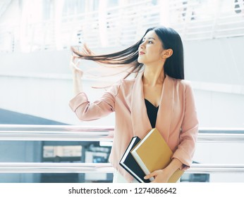 Portrait Smart working women in pink suit flick hair confidently in the morning.