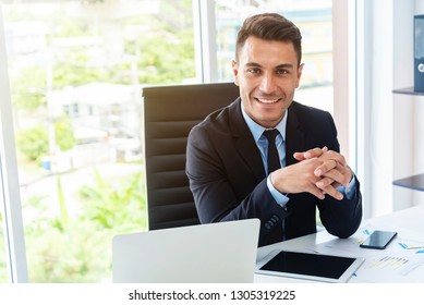 Portrait of smart young businessman smiling with technology device on desk in modern office.