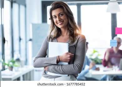 Portrait of smart young businesswoman looking at camera while holding her notebook on coworking place.