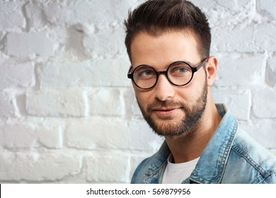 Portrait of smart young caucasian man in glasses.