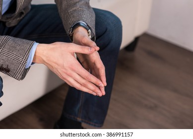 Portrait of a smart young man sitting with crossed hands closeup