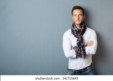 Portrait of a smart young man wearing a scarf standing with arms crossed against blue background