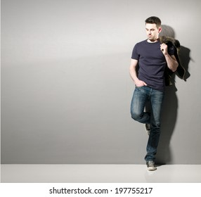 Portrait of a smart young man wearing jeans and shirt standing against grey background