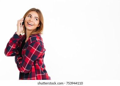 Portrait of a smhappy casual girl talking on mobile phone while looking away at copy space isolated over white background