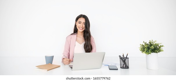 Portrait smile beautiful business asian woman in pink suit working in office desk virtual computer. Small business owner people employee freelance online sme marketing e-commerce telemarketing concept