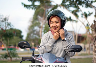 portrait of smile hijab  woman wearing and clicking a helmet belt before riding a motorcycle in a park on a sunny day