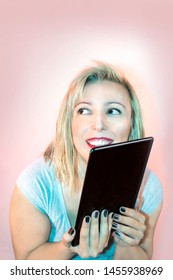 Portrait of a smiled blonde woman holding a tablet
