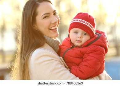 Portrait of a smiley mother posing with her baby keeping warm wearing a red jacket outdoors in winter