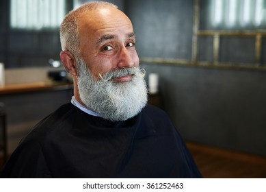 portrait of smiley senior man with grey-haired beard and mustache in barbershop