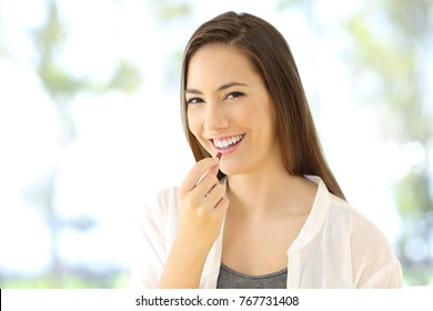 Portrait of a smiley woman taking a pill looking at you