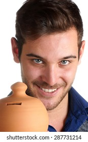 Portrait of a smiling 20 years old caucasian young man with blue eyes holding a clay moneybox. Over a white background